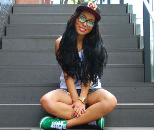Pretty ebony with flowing tresses and hot sexy body poses in glasses, black cap, white top, blue denim shorts, and green Nike shoes