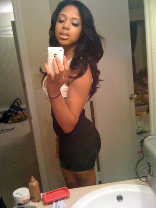 Pretty ebony with flowing wavy tresses, perky boobs, ample bouncy booty, and slim sexy curvy hot body takes selfie in short tight black/white dress