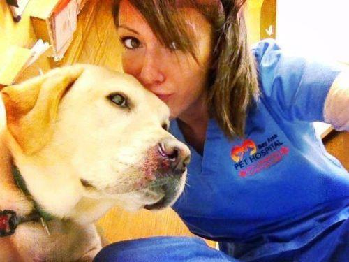 Pretty brunette kisses dog and takes selfie in blue nurse/doctor uniform