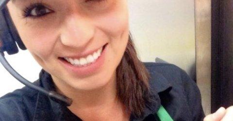 Brunette takes selfie in black top, cap, and microphone headset