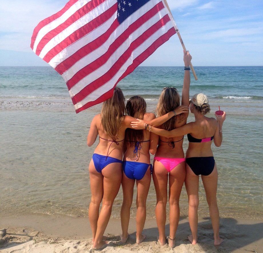 Chivettes in bikinis wave American flag at beach