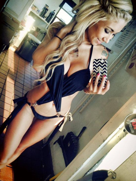 Blonde with perky round juicy big boobs, flat abs, slender legs, and slim sexy curvy host body takes selfie in cleavage showing black bikini swimsuit