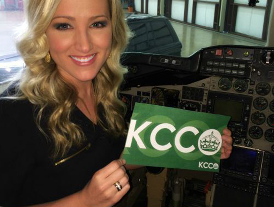 Blonde in black top smiles and poses with green KCCO sign
