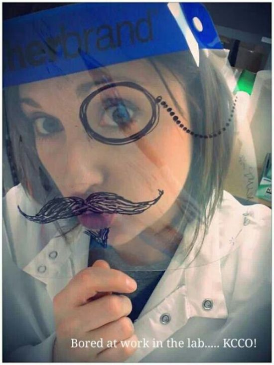 Brunette in white top takes selfie behind transparent plastic sheet with drawing of moustache and one-eyed glasses