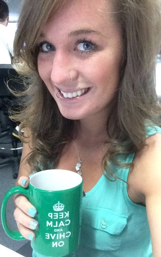 Pretty light-eyed blonde with nose ring takes selfie in turquoise top with green KCCO cup