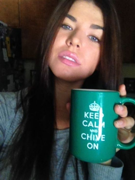 Light-eyed brunette with juicy pink lips takes selfie in grey top with green KCCO cup