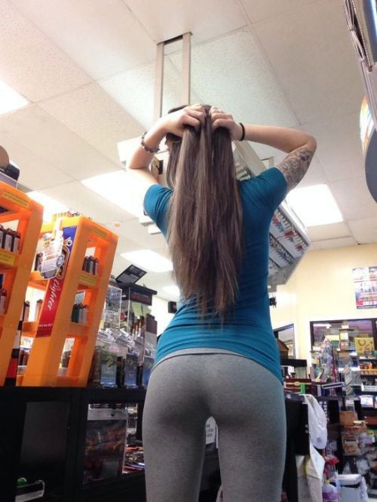 Tattooed brunette with flowing tresses, perky round juicy butt cheeks, and slim sexy curvy hot body strikes a pose in blue top and grey yoga pants