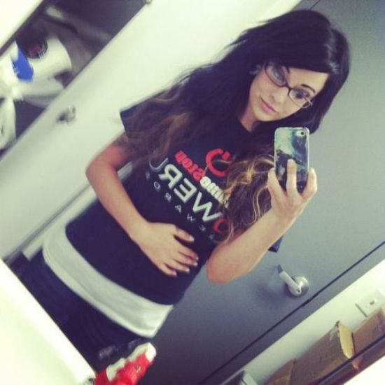 Pretty brunette with flowing tresses and slim sexy body takes selfie in glasses, black/white top, and jeans