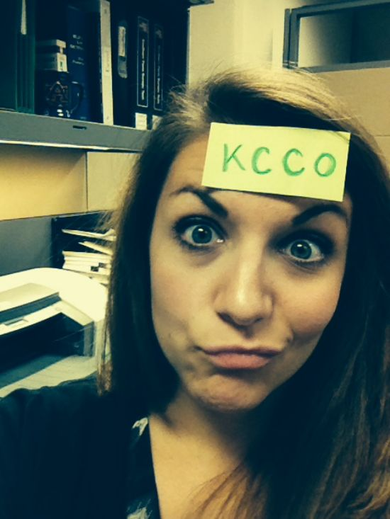 Brunette with KCCO sign on forehead makes a face and takes selfie in black top