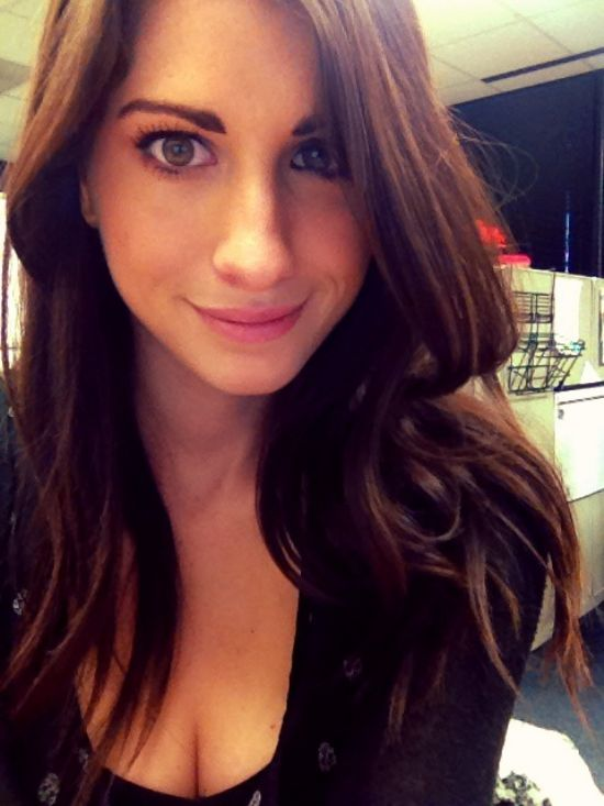 Pretty brunette with flowing wavy tresses and pink full lips takes selfie in cleavage showing black top