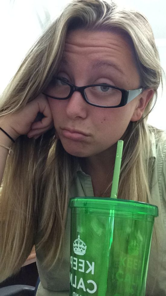 Light-eyed blonde makes a face and poses in glasses and beige top with a green KCCO cup