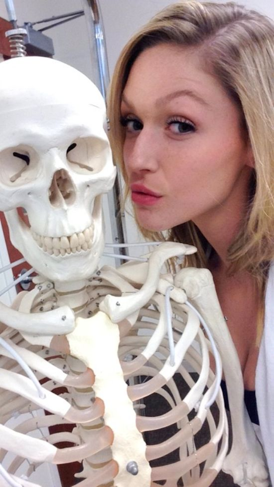 Brunette with perky boobs in black top and red jacket poses with a skeleton