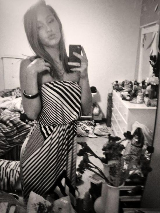Brunette with slim sexy body takes selfie in striped dress in a messy room
