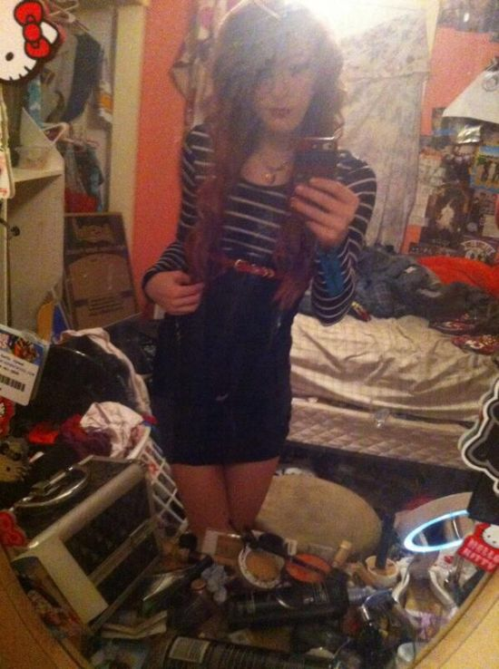 Brunette with slim sexy body takes selfie in black/white short tight dress in a messy room