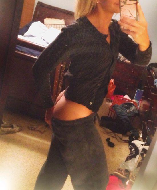 Blonde with slim sexy body in black top pulls down black pants to selfie perky juicy naked butt cheeks