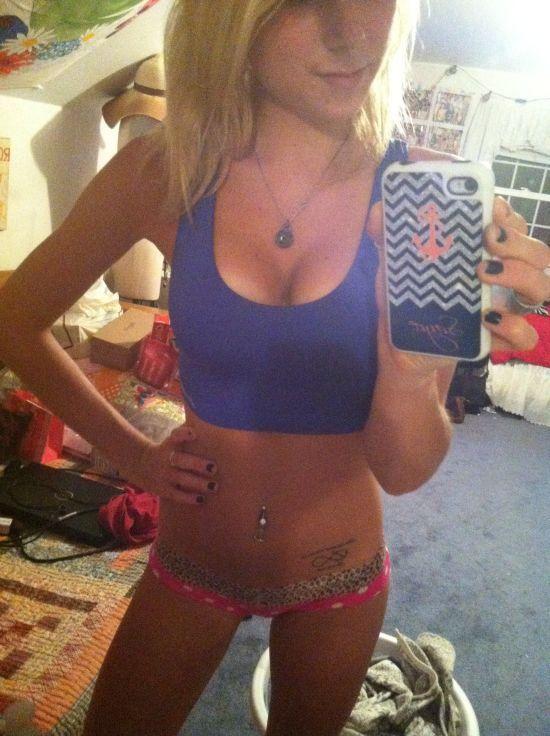 Blonde with perky juicy big boobs, flat abs, slender legs, and slim sexy hot body takes selfie in indigo sports bra and pink/black panties