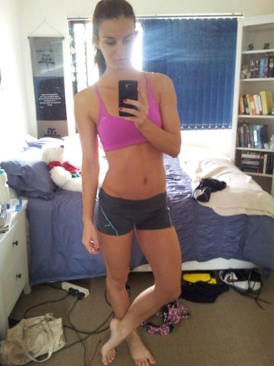Brunette with perky boobs, flat abs, slender legs, and slim sexy hot body takes selfie in magenta sports bra and black yoga shorts