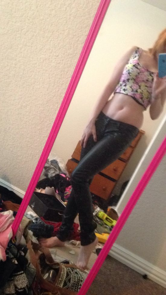 Blonde with flat abs, slender legs, and slim sexy body takes selfie in pink colorful crop top and black latex pants in messy room
