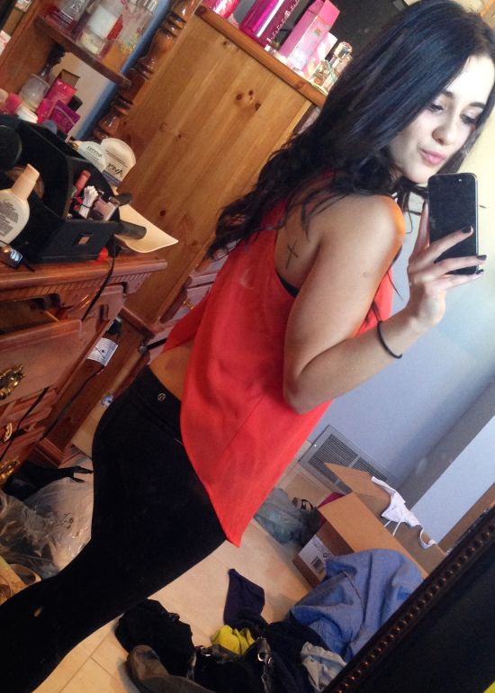 Brunette with slim sexy body in red top and black pants takes selfie in messy room
