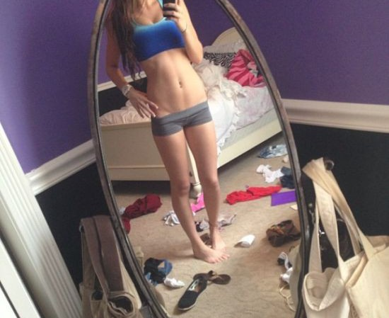 Brunette with long tresses, perky boobs, flat abs, slender legs, and slim sexy body takes selfie in blue sports bra and grey/black yoga shorts