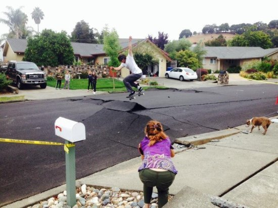 Guy skateboarding on big crack in the street