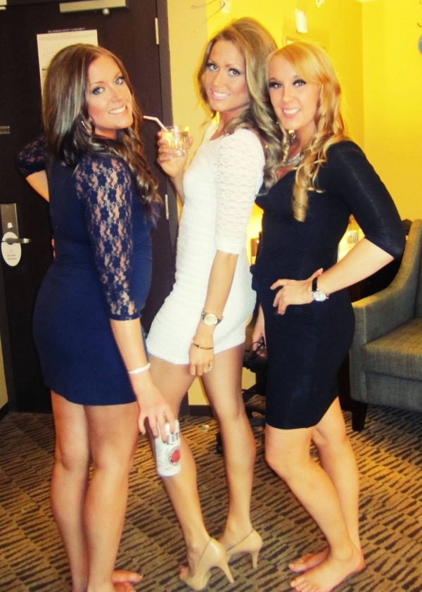 Three girls in white, black, and blue dresses