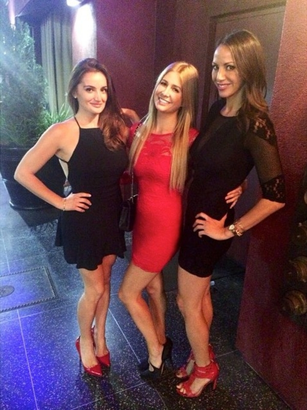 Girl in red dress with two girls in black dresses