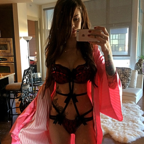 Brunette with black lingerie and pink bath robe takes selfie in living room