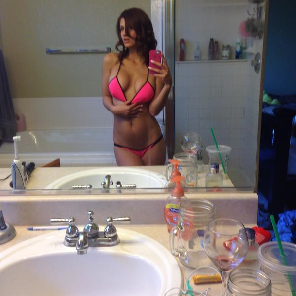 sexy figured lady tugs her bra to click perky boobs selfie in bathroom