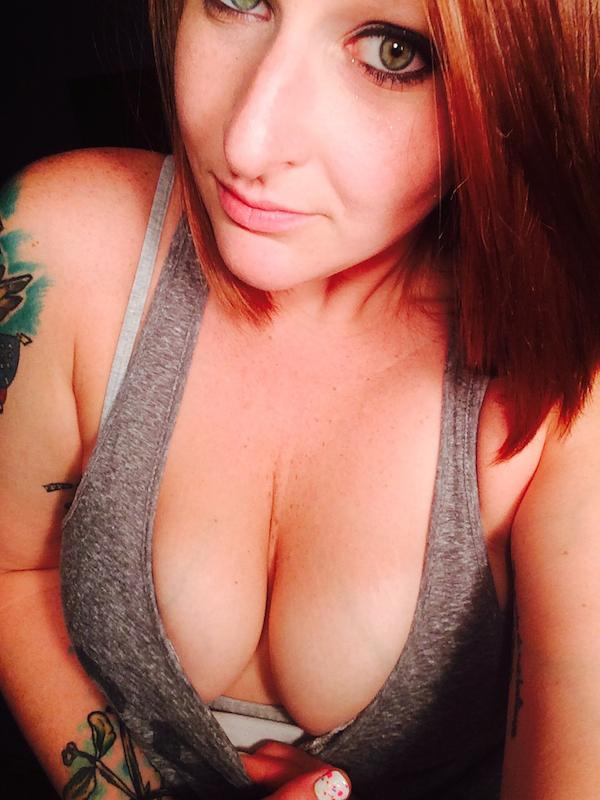 sexy green eyed woman tugs her top to click selfie to show her sexy round boobs