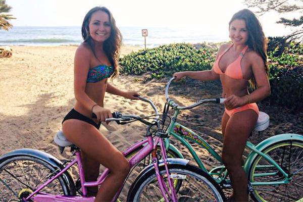 Hot bikini girl making pose on bicycle near the beach