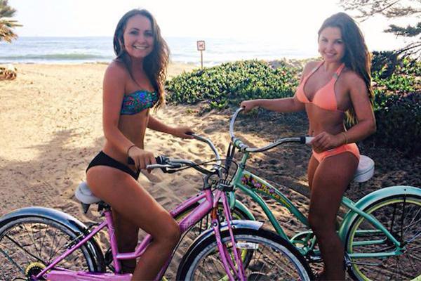 Hot bikini girl making pose on bicycle near the beach