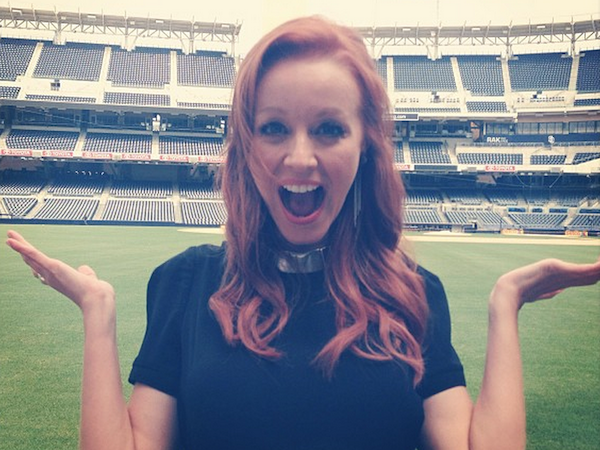 pretty girl Lindy booth poses with surprise facial expression wth a wide open mouth in a lush green playground
