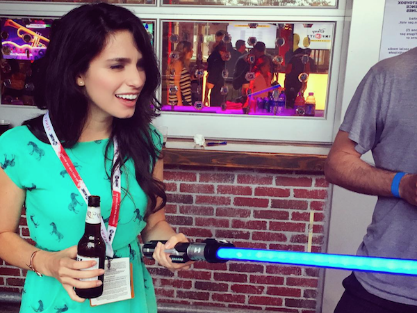 Pretty brunette with a beer in one hand and a light saber in other poses in blue dress