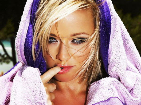 Pretty sultry blonde with beautiful light eyes and juicy red lips poses with lavender/purple towel on head