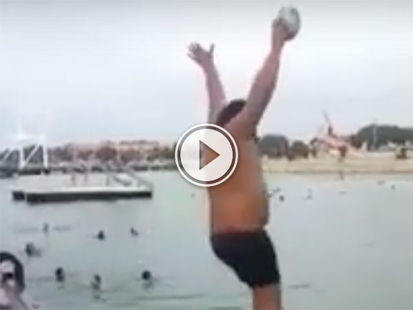 Man jumps into a lake with a ball and ball rockets up (Video)