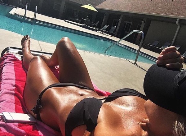 Glossy and tanned hot body in black bikini by the pool