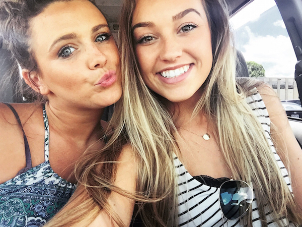 two friends click selfie in a car pouting and smiling for the camera