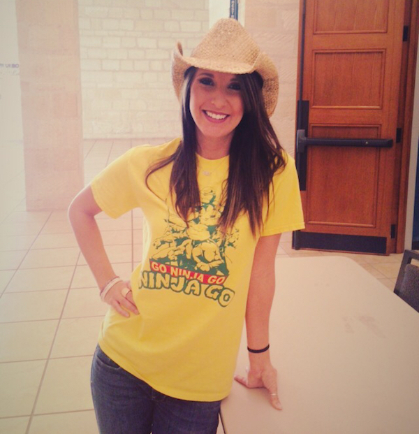 Cute brunette with slim sexy body poses in beige Cowboy hat, blue jeans, and yellow 'Ninja Turtles' tee