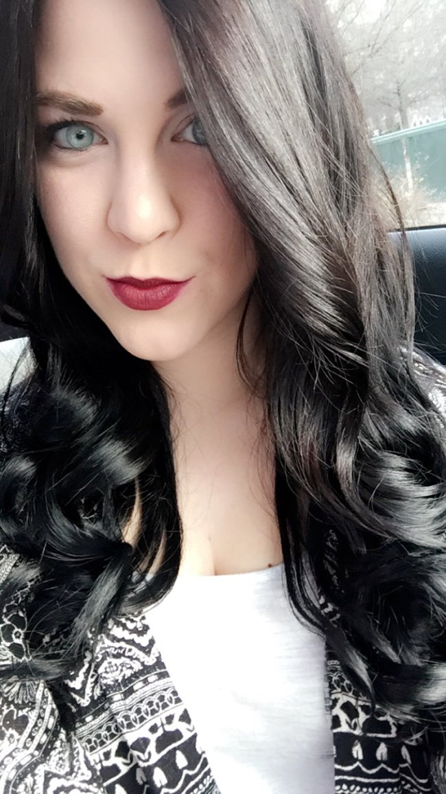 Cute light-eyed brunette with red juicy lips and flowing tresses takes selfie in white top and black jacket
