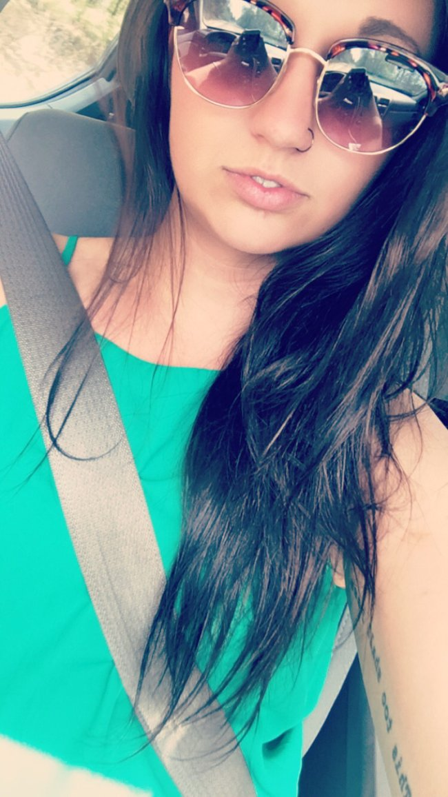 pretty chick with nosering taking selfie in the car in cateye sunglasses