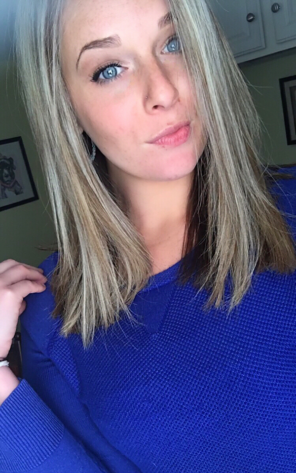 Blonde beauty with blue eyes and wearing blue top clicks a selfie