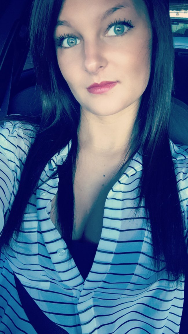 Cute brunette with beautiful light eyes and red juicy lips takes selfie in cleavage showing white striped top