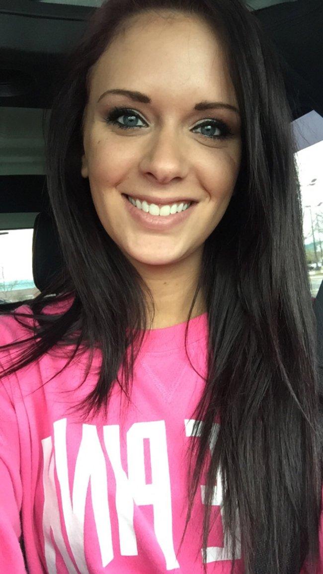 Cute light-eyed brunette smiles for selfie in pink top