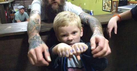 Little boy shows his fists locked together, with the words 'Thuglife' written on them, as  a man with tattoed hand looks on.