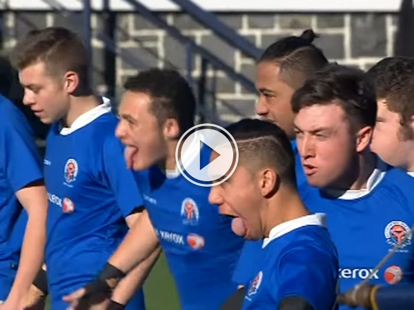 Boys in blue jerseys stick out their tongues and stare angrily at someone or something!