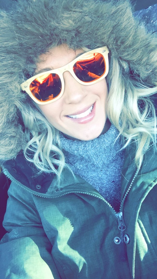 Girl in huge furry eskimo jacket and thick rimmed sunglasses