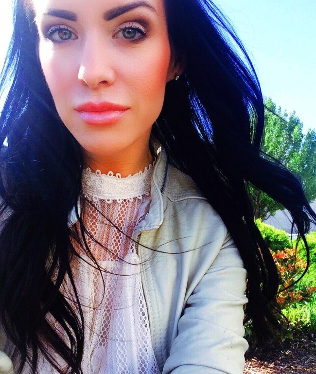 Gorgeous brunette with beautiful light eyes and plump juicy lips takes selfie in white lace top and greyish-beige jacket
