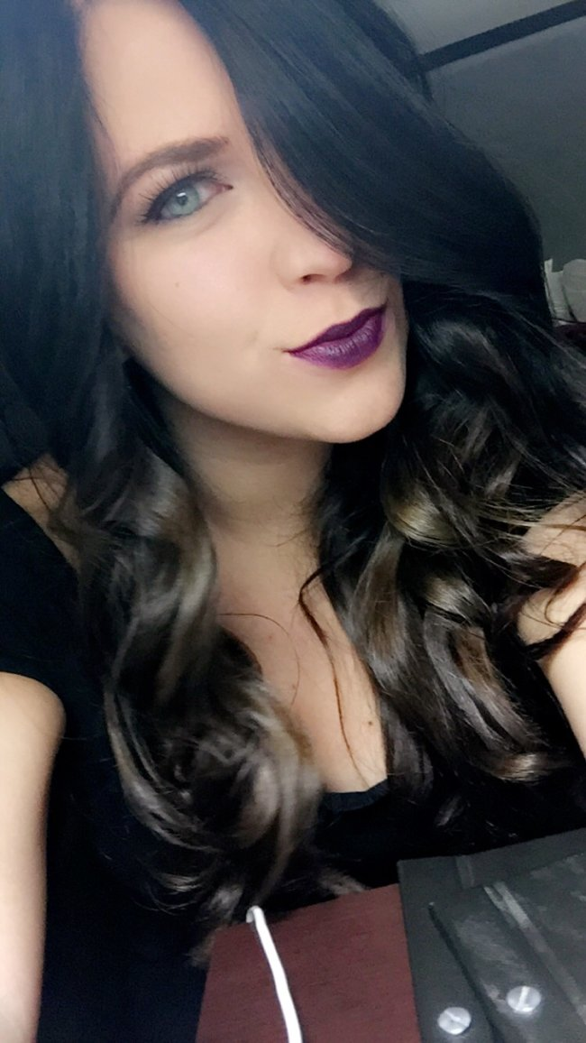 Cute light-eyed brunette with purple lipstick and flowing tresses takes selfie in black top