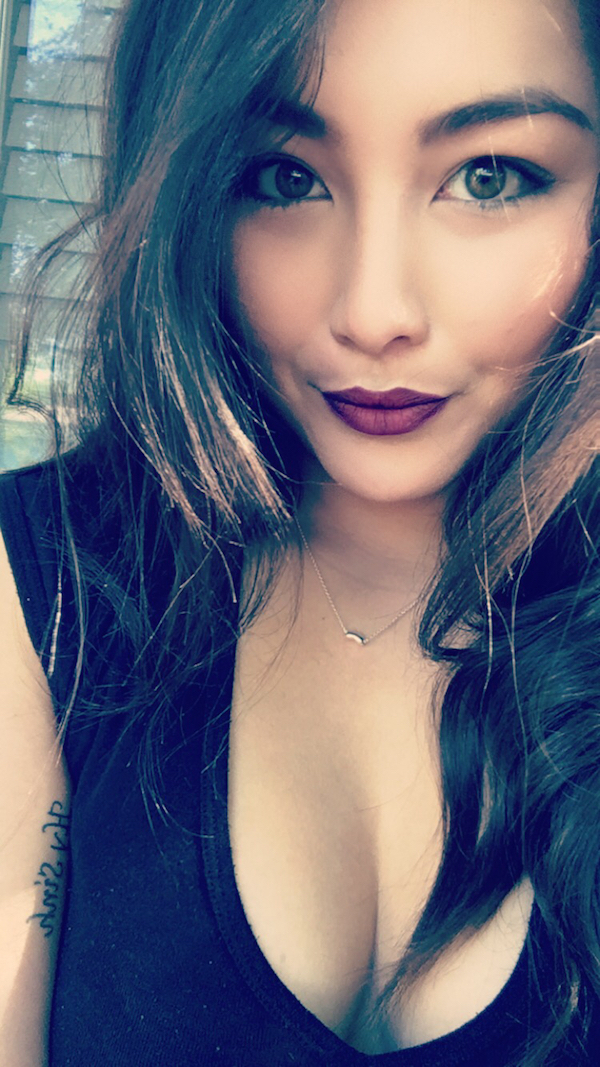Cute light-eyed brunette with red juicy lips and supple boobs takes selfie in cleavage showing black top